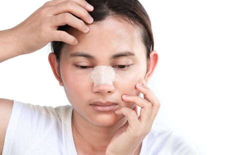 Close up face of asian woman with nose plastic surgery for beauty and cosmetic conept, white background Stock Photo