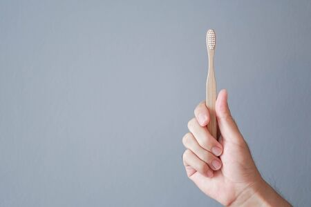 Closeup man hand holding wooden toothbrush with grey background, health care concept 스톡 콘텐츠 - 128849351