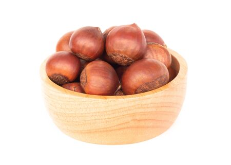 Closeup horse chestnuts in wood bowl isolated on white background,  healthy food concept