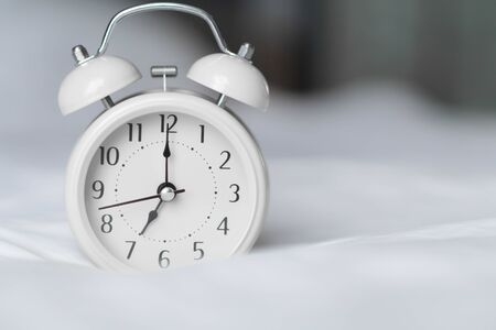 Alarm clock on white bad for wake up time with light from window, selective focus 스톡 콘텐츠