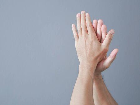 Man handen klappen op grijze achtergrond