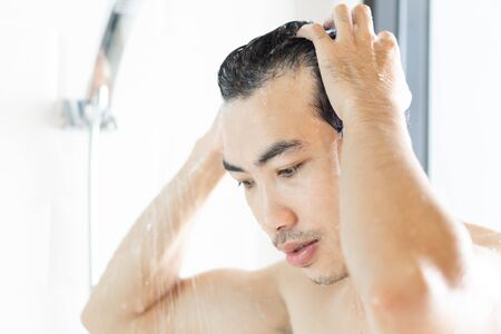 Closeup young man washing hair with with shampoo in the bathroom, vintage tone, selective focus Stockfoto