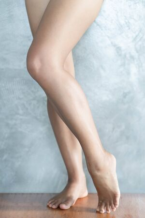 Closeup woman legs relaxing with grey background, beauty and skin care concept, selective focus