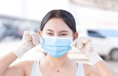 Closeup woman wearing face mask for protect air polution or virus covid 19 with white glove in car park of supper market  background, health care and medical concept