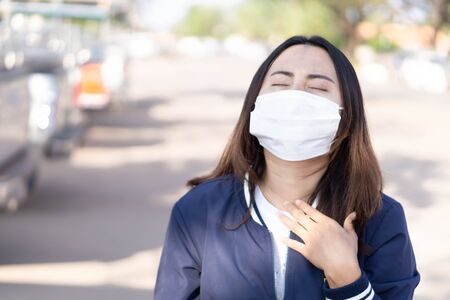 Closeup woman wearing face mask for protect air polution or virus covid 19 with chest pain , health care and medical concept