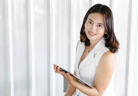Business woman hand holding digital tablet computer with graph of Binary option for trading platform, setective focus