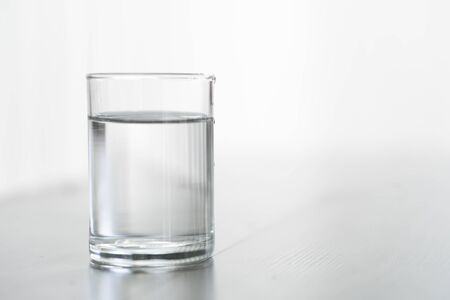 Glass of water on wood table with light in the morning, healthy care concept, selective focus 免版税图像