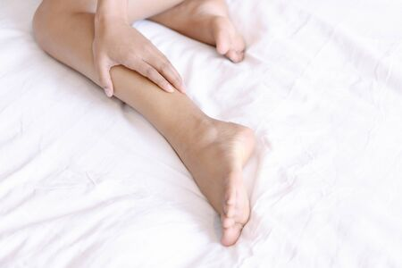 Close up woman touching her leg with pain lying on white bed, health care concept