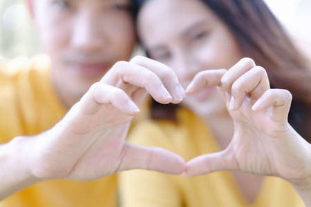 Closeup of couple making heart shape with hands in the park
