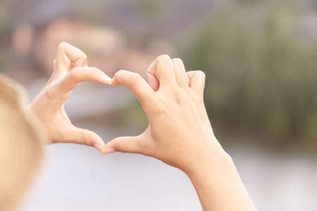 Closeup hand make heart shape with nature background, selective focus