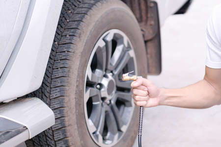 Close up man hand holding mechanic inflating tire and checking air pressure with gauge pressure in service station