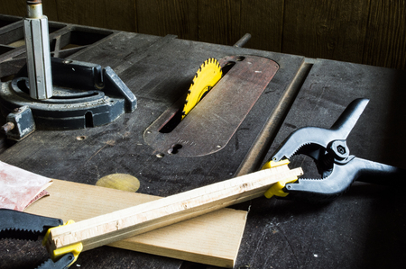clamped: Wood clamped together placed on a table saw with sand paper Stock Photo