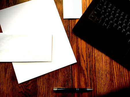 writing materials: Laptop keyboard on desk with hand written letter writing materials