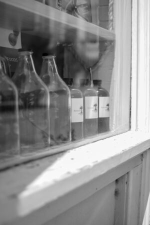 Glass bottles lined up for display in a vendor window