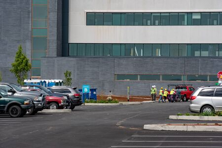 Workers at UMPC Hospital consntruction site unloading a bin