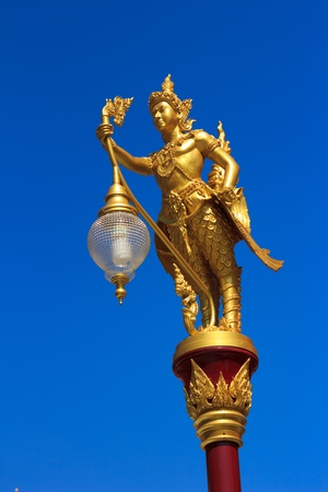 male deity with lamp in thai temple. photo