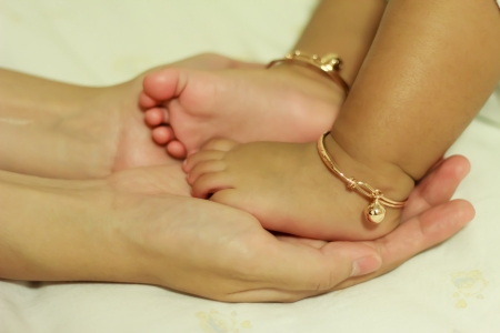 Mother s hand and baby foot with anklet photo