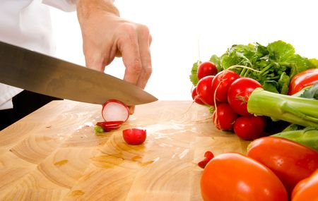 Professional chef slicing radish in front of white background photo