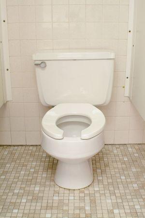 White toilet in stall on tile floor. photo