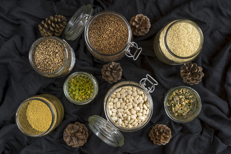 Beans, seeds and grains in jars on black background