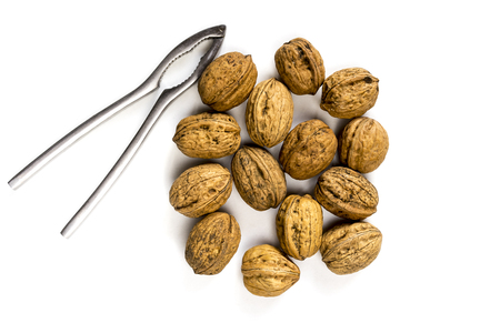 Walnuts and nutcracker on white background
