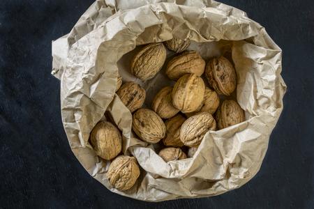 Walnuts inside a paper bag on black table Stok Fotoğraf