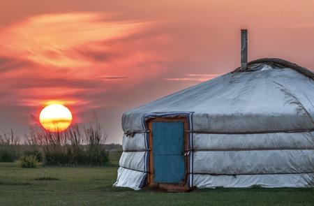 La puesta de sol cae sobre una yurta en la estepa mongola Foto de archivo - 87720010