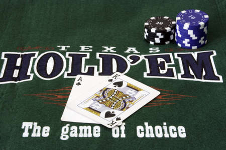 A green mat with card and chips with poker written on it photo