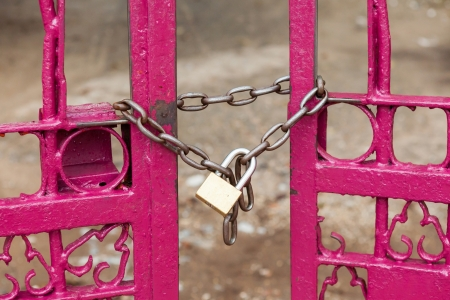keep gate closed: Close up chain locked on pink color fence gate