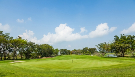 golfcourse: Beautiful golf course green and blue sky in bright sunlight Stock Photo