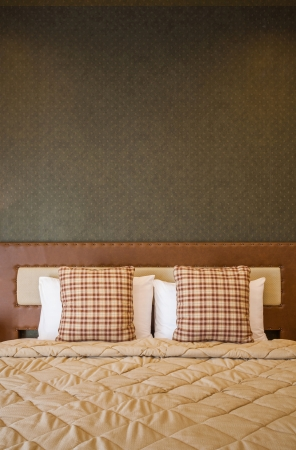 Pillows on double bed in vintage style bedroom photo