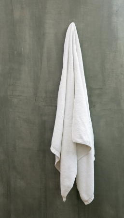 Hanging White Towel draped on Exposive Concrete Wall in the Bathroom photo