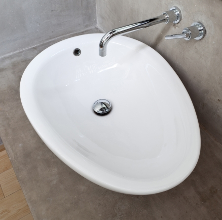 White Oval Basin in Exposed Concrete Wall Bathroom photo