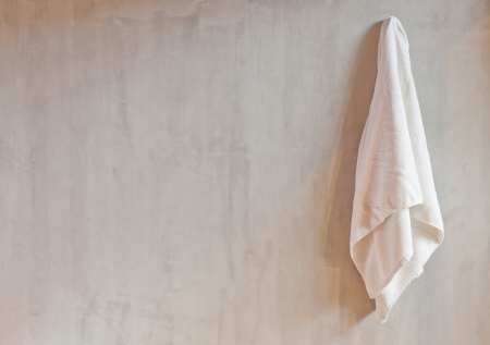 towel: Hanging White Towel draped on Exposed Concrete Wall in the Bathroom