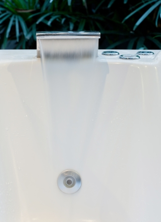 Modern Spa Tub Faucet with Running Water and Control Buttons photo