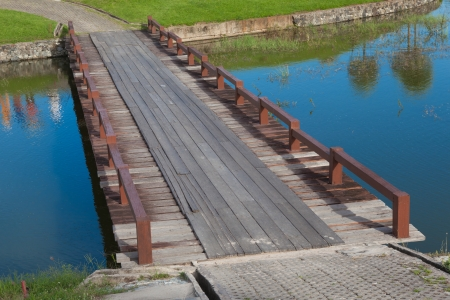 Wood Bridge Over the Water in Golf Course with Reflex of Golfer, Thailand photo