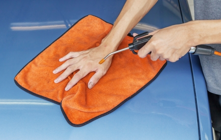 Worker Cleaning Car Using Microfiber Cloth And High Pressure Air Blower photo