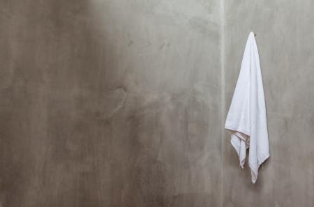 バス ルームの壁の角の近く白いタオルをぶら下げ 写真素材