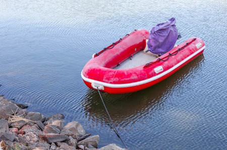 tightened: Red rubber inflatable boat was tightened at the waterside.