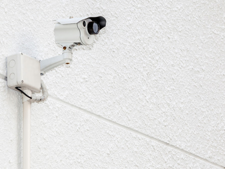 Security camera, CCTV on the white cement wall with electric line photo
