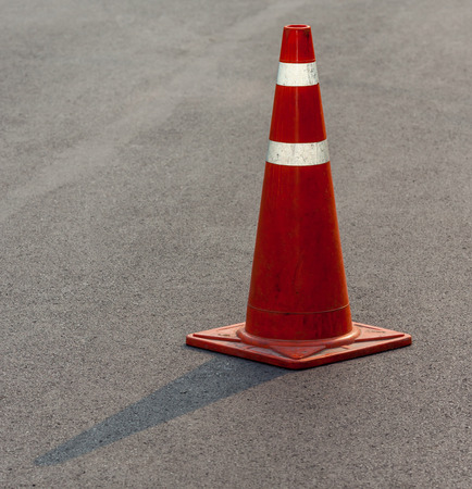 Grunge traffic cone with double white stripe on the street, with space for text photo