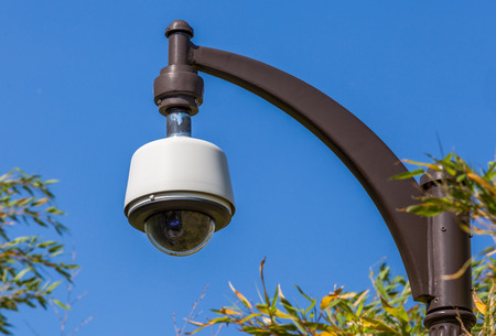 Security camera, CCTV hangs in park for monitoring with the blue sky background photo