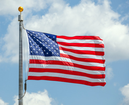 The American flag waving against a blue sky on a flag pole, focus on star of waving flag