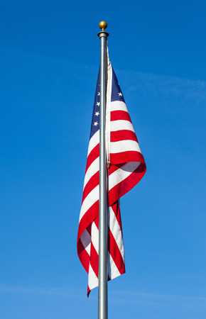 American flag with flag pole on clear blue sky background photo