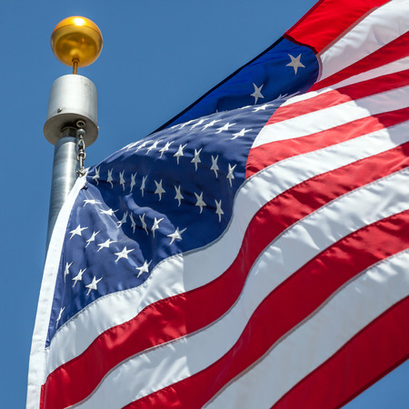 Close-up American flag blows in the wind with flag pole, focus on star of waving flag