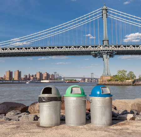 segregate: Recycle bins for different kind of garbage with the Manhattan Bridge Background
