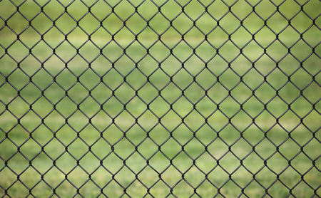 Metal fence with Green grass field background for protection, use as the background