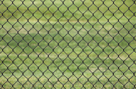 Metal fence, Detail of metal fence in a Green grass background, use as the background photo