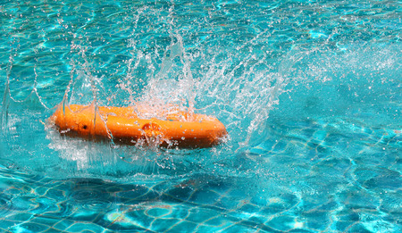 emergency case: Orange life buoy is splashing with clear blue water in swimming pool, for the emergency case