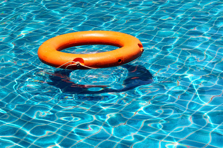 emergency case: Bright orange life buoy floating on the surface of blue water swimming pool, for the emergency case Stock Photo